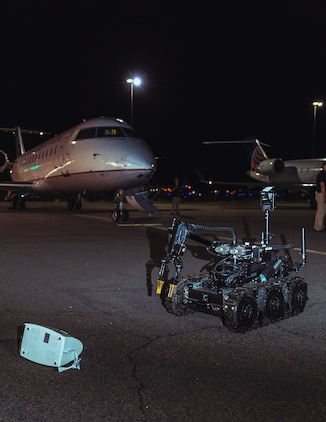 A remote-controlled robot examines a possible home-made explosive during at Operation Bono at Palm Springs International Airport, Palm Springs, Calif., July 13, 2018. The purpose of Operation Bono is to provide unique training opportunities for federal, state, and local public safety bomb squads and military explosive ordnance disposal teams, as well as facilitates training and drills designed for bomb squads to employ their tactics while operating in the aviation domain in, and around PSP airport. (U.S. Marine Corps photo by Lance Cpl. Rachel K. Porter)