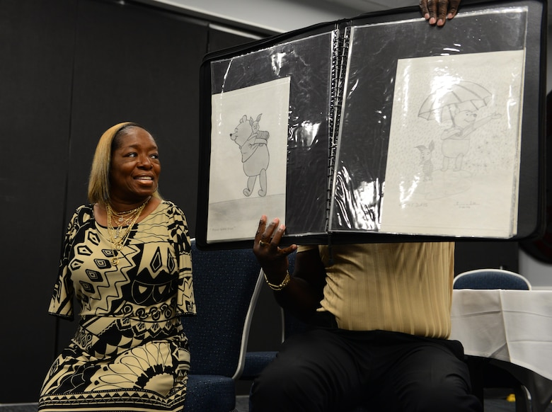Tawana Williams, motivational speaker, and her husband, Toby, showcase her artwork July 16, 2018, at Columbus Air Force Base, Mississippi. Williams demonstrated how she cared for a child, signs her name and tied a young boy's shoes all with just her feet. (U.S. Air Force Photo by Airman 1st Class Beaux Hebert)
