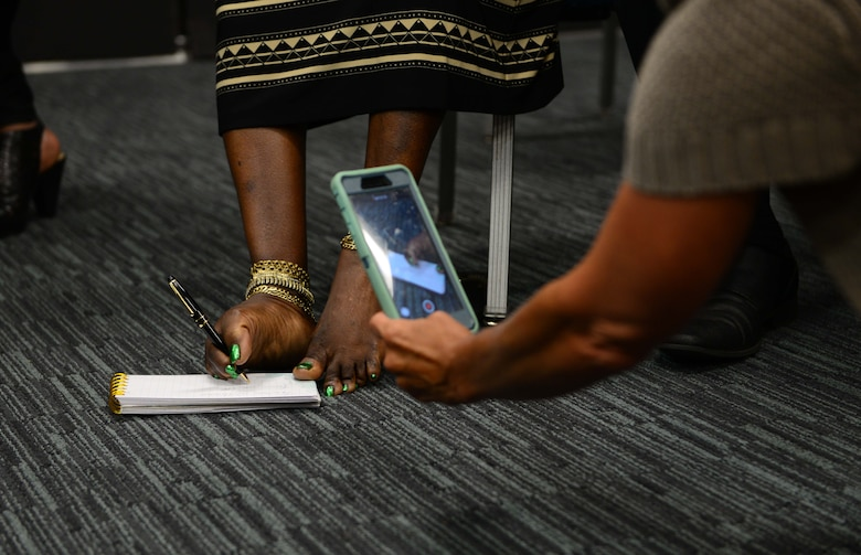 Tawana Williams, motivational speaker, demostrates how she signs her name to attendees July 16, 2018, at Columbus Air Force Base, Mississippi. Born without arms, Williams learned how to care for herself, and later on her daughter, with her feet. (U.S. Air Force Photo by Airman 1st Class Beaux Hebert)