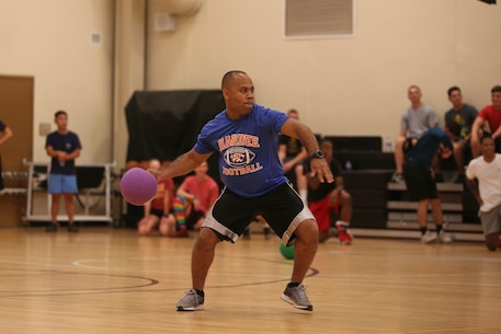 A Marine throws a dodgeball as part of a tournament for the Semper Fit Summer Challenge aboard Marine Corps