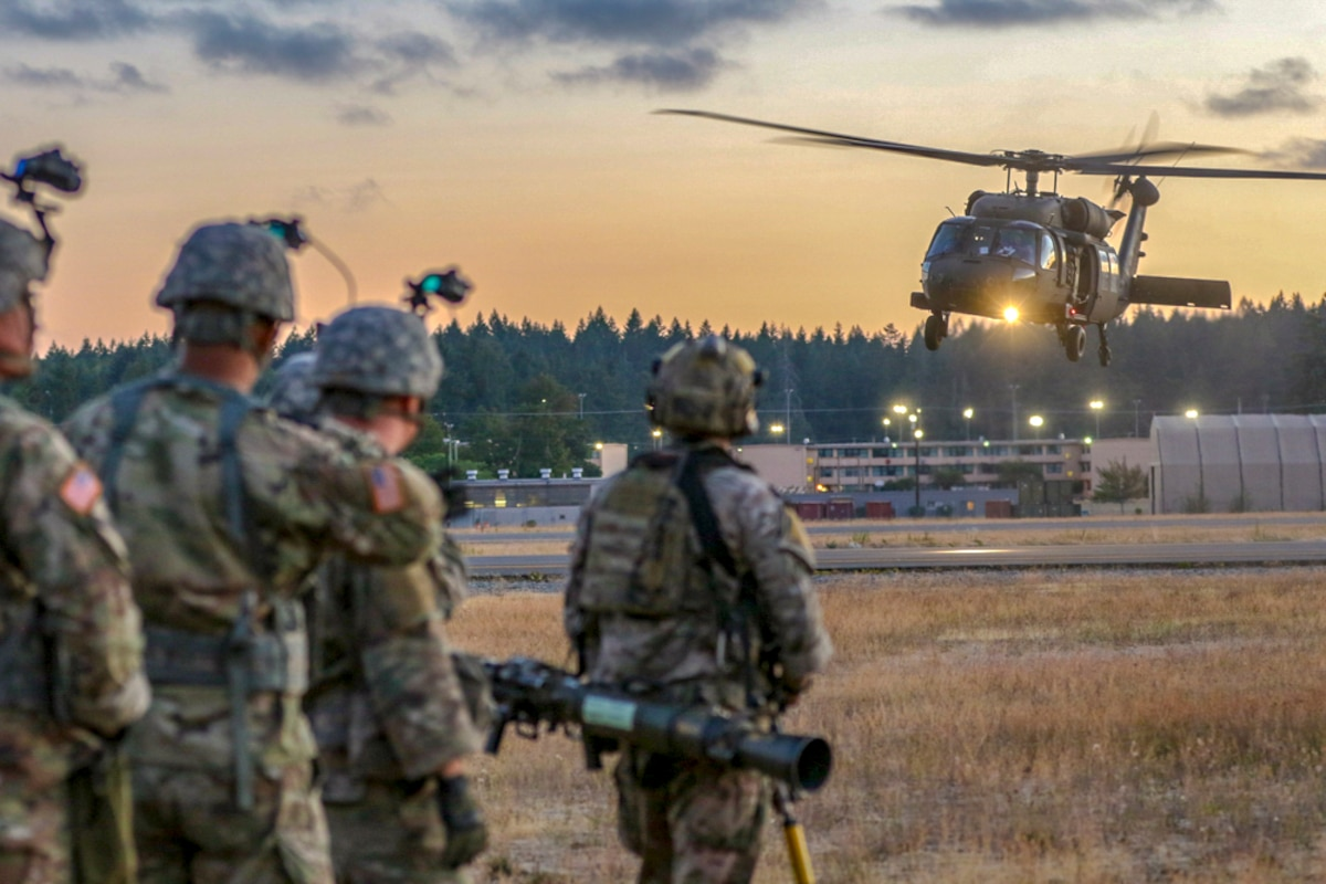 A helicopter lands in the background with soldiers waiting.