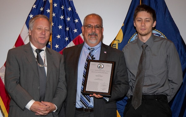 """IMAGE: DAHLGREN, Va. (July 19, 2018) - John Fiore, Naval Surface Warfare Center Dahlgren Division (NSWCDD) technical director, holds a plaque reproduction of the patent certificate he presented to Gerhard Thielman and his son, Benjamin, at the NSWCDD Patent Awards ceremony. The father and son team were among 32 patent holders honored before family, friends and colleagues at the NSWCDD Patent Awards ceremony. """"The potential benefit to the warfighter is an adaptable, self-contained vehicle with multi-mission capability,"""" said NSWCDD Chief of Staff Chuck Campbell regarding the Thielmans' innovation.  (U.S. Navy photo by Ryan DeShazo/Released)"""