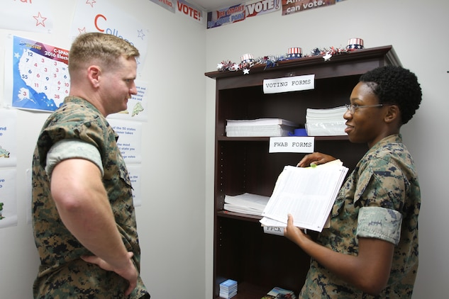 U.S. Marine Corps SSgt. Chris Light (left) spoke to LCpl. Mykkeria Johnson (right) by the Marine Corps Logistics Base Albany Adjutant Office to learn how to vote ahead of the general election in Georgia. The Adjutant Office held the 2nd annual Voting Convention for Marines and civilian-Marines, July 19. The event is part of an annual training for all active duty personnel. (U. S. Marine Corps photo by Re-Essa Buckels)