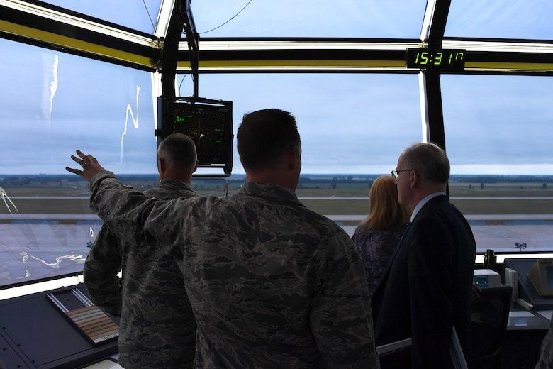 Dominic Pohl, 25th Air Force executive director, right, observes the base geography and flight line through the air traffic control tower windows July 20, 2018, on Grand Forks Air Force Base, North Dakota. Air traffic controllers shared their day-to-day operations with Pohl, detailing how they manage the air space and communicate with aircraft. (U.S. Air Force photo by Airman 1st Class Elora J. Martinez)