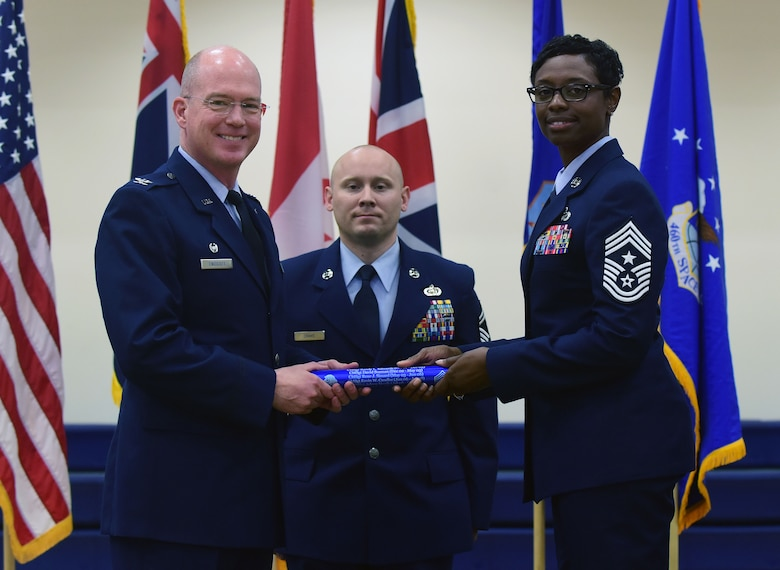 Chief Master Sgt. Tamar Dennis, 460th Space Wing command chief, accepts the baton from Col. Troy L. Endicott, 460th SW commander, symbolizing the change of leadership on Buckley Air Force Base, Colorado, July 20, 2018.