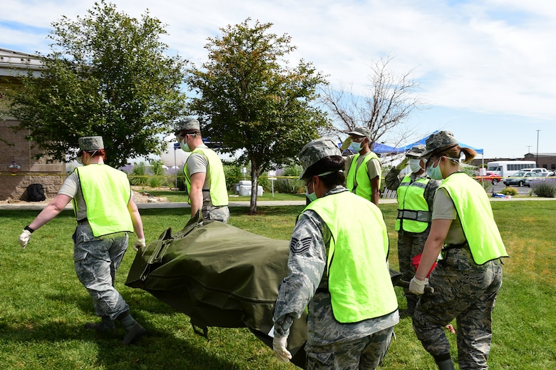 Airmen from the 460th Force Support Squadron carry a simulated corpse out of a cordoned area as part of search and recovery training on July 19, 2018, on Buckley Air Force Base, Colorado. The training ensures Airmen are prepared for crisis response situations. (U.S. Air Force photo by Senior Airman AJ Duprey)
