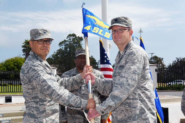 Col. Curtis Hernandez, 30th Operations Group commander, hands the guide on to Lt. Col. Kenneth Decker, 4th Space Launch Squadron commander, during the 30th Launch Group deactivation ceremony on July 20, 2018, at Vandenberg Air Force Base, Calif. The 30th Space Wing inactivated the 30th LCG, merging their range responsibilities and personnel with the 30th OG. (U.S. Air Force photo by Tech. Sgt. Jim Araos/Released)
