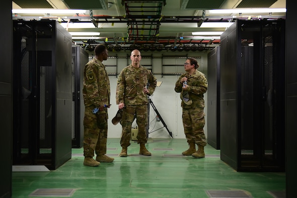 Three Airman stand in a brand new building