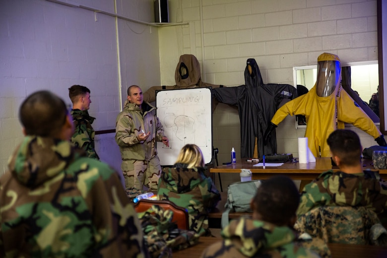 Cpl. Tyler J. Beard, center-left, instructs Marines on the sampling and testing of chemicals during a reconnaissance, surveillance and decontamination (RSD) course conducted by chemical, biological, radiological and nuclear (CBRN) Marines with Combat Logistics Regiment 35, 3rd Marine Logistics Group July 18, 2018 at Camp Kinser, Okinawa, Japan. The RSD course ensures that Marines can effectively detect and decontaminate a CBRN environment and save lives of contaminated Marines in an area. Beard, a native of Pearland, Texas, is a CBRN defense specialist with CLR-35. (U.S. Marine Corps photo by Pfc. Terry Wong)