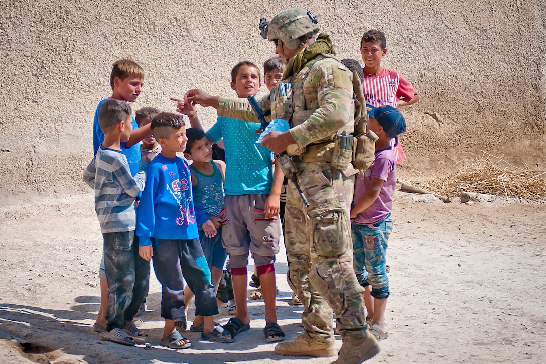 A soldier stands with a group of children.