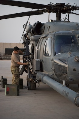 An Airman with the 801st Expeditionary Maintenance Squadron loads an HH-60 Pave Hawk's machine gun with training rounds for a nighttime exercise, July 4, 2018, at Al Asad Air Base, Iraq.