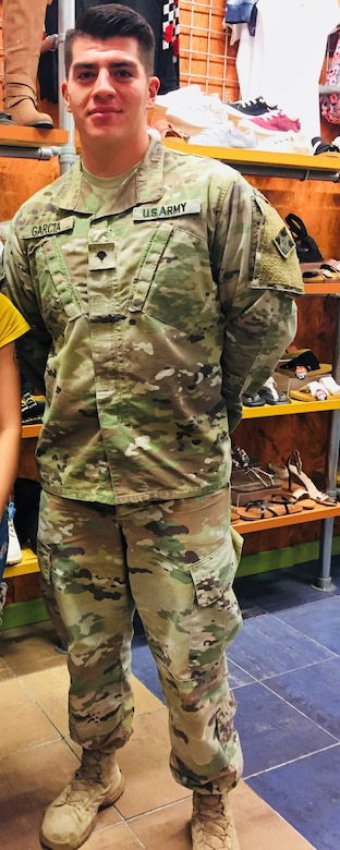 A soldier in camouflage stands in a store.