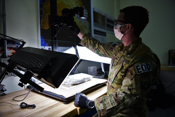 Master Sgt. Michael Breive, Forensic Exploitation Laboratory – CENTCOM non-commissioned officer in charge, prepares to photograph a piece of evidence June 27, 2018 at the FXL-C lab, located on Camp Arifjan, Kuwait. Breive is the sole Airman at the FXL-C office, serving in a joint expeditionary tasked and individual augmentee role. (U.S. Air Force photo by Staff Sgt. Christopher Stoltz)