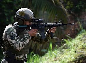 A Paraguayan comando shoots targets during a stress shoot event during Fuerzas Comando
