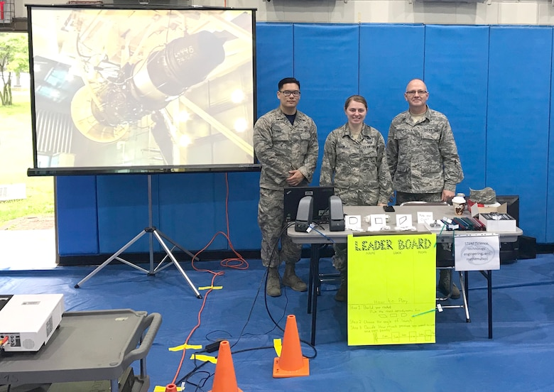2nd Lt. Jimyung Park, 2nd Lt. Ashley Olson, Senior Master Sgt. Darrell Townsend man their booth at the Osan Science, Technology, Engineering and Mathematics (STEM) Career Day held for students of military families at the base in South Korea. As part of the STEM event, Townsend, who is a craft superintendent at Arnold Air Force Base in addition to serving in the Tennessee Air National Guard, helped demonstrate how to launch straw rockets. The materials for the demonstration were provided by Olga Oakley, Air Force STEM director at Hands-On Science Center. (Courtesy photo)