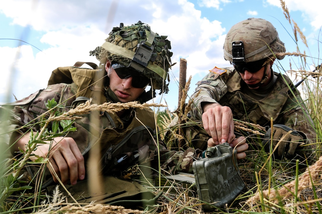 A U.S. and British soldier position an M18A1 Claymore mine.