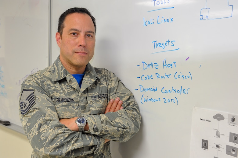 Master Sgt. Robert Beveridge, non-commissioned officer in charge of the 910th Communications Squadron's cyber systems operations section, poses for a photo in front of a white board used for cyber defense training here, July 14.