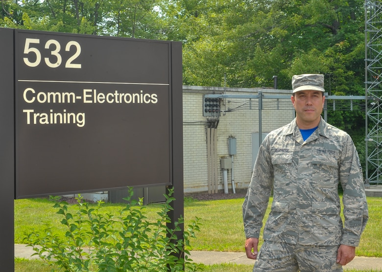 Master Sgt. Robert Beveridge, non-commissioned officer in charge of the 910th Communications Squadron's cyber systems operations section, poses for a photo in front of his work center here, July 14.