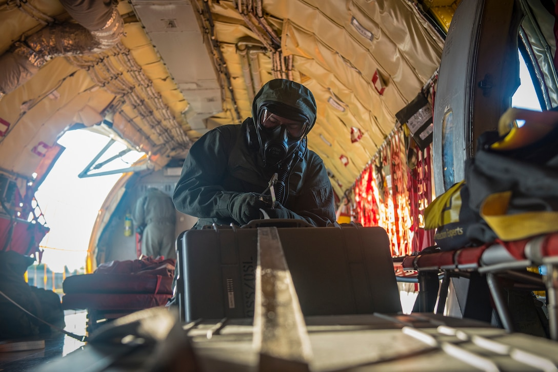 Senior Airman Stetson Vigil, 93rd Air Refueling Squadron boom operator, secures cargo during the first in-field use and test of the new Joint Service Aircrew Mask on a KC-135 Stratotanker at Fairchild Air Force Base, Washington, July 17, 2018. The gear enhances the ability to operate because of the reduced footprint of the gear while still allowing maximum protection. (U.S. Air Force photo/ Airman 1st Class Whitney Laine)