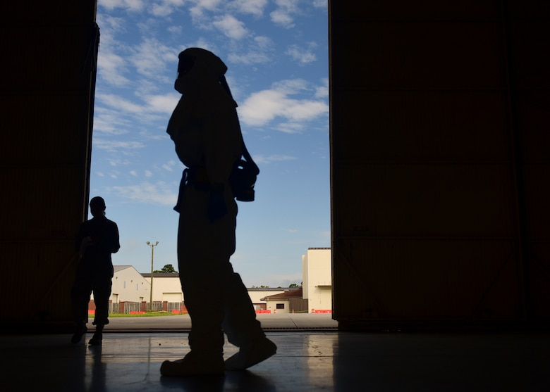 Staff Sgt. Brian Groll, 375th Aeromedical Evacuation technician out of Scott Air Force Base Ill. walks through a hangar at Joint Base Charleston, S.C. July 18, 2018. Groll donned necessary personal protective equipment during an exercise dealing with the transport of highly infectious patients.
