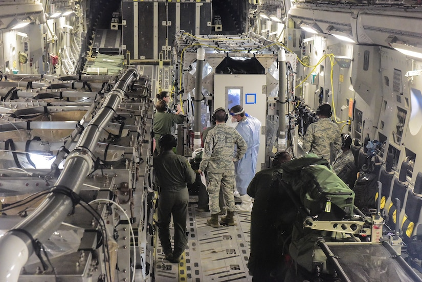 Airmen from the 628th and 375th Aeromedical Evacuation Squadrons out of Joint Base Charleston, S.C. and Scott Air Force Base Ill., along with medical researchers from Indiana and Nebraska universities conduct Transportation Isolation System training July 18, 2018 on a flight from Joint Base Charleston to Offutt Air Force Base, Neb. The Transport Isolation System, or TIS, is an enclosure the Department of Defense can use to safely transport patients with highly contagious diseases such as Ebola.