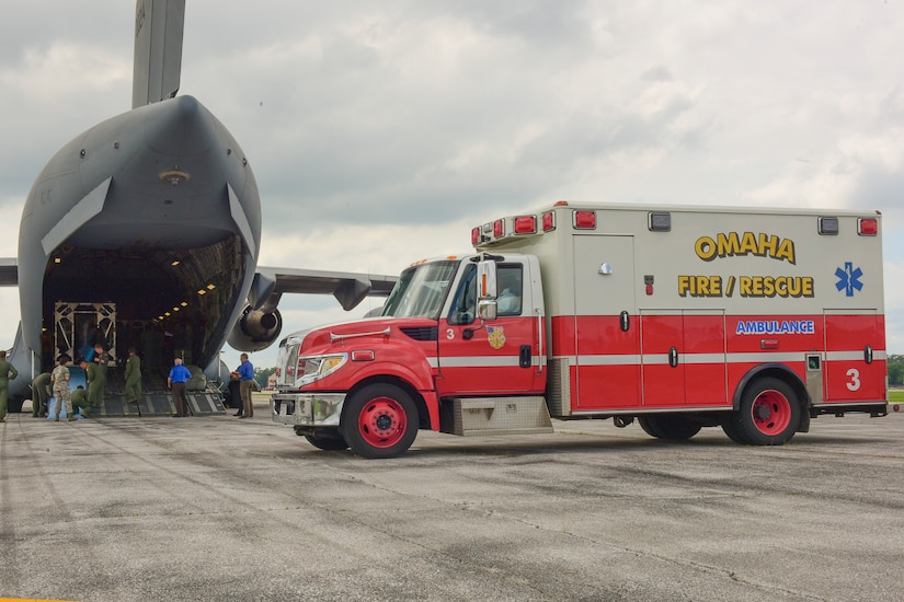 Airmen from the 628th and 375th Aeromedical Evacuation Squadrons prepare to transfer simulated patients from a Transportation Isolation System on a C-17 Globemaster III to an ambulance during an exercise July 18, 2018 at Offut Air Force Base, Neb. The TIS is an enclosure the Department of Defense can use to safely transport patients with highly contagious diseases.