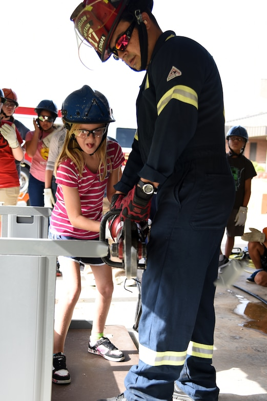 17th Civil Engineer Squadron firefighter captain, Daniel Chapa III, helps junior firefighter, Hailey Hascall, cut through a desk during the Junior Firefighter Camp at the Fire Station on Goodfellow Air Force Base, Texas, July 17, 2018. During the camp, the children learned about the firefighting profession and how to stay safe around fires. (U.S. Air Force photo by Staff Sgt. Joshua Edwards/Released)