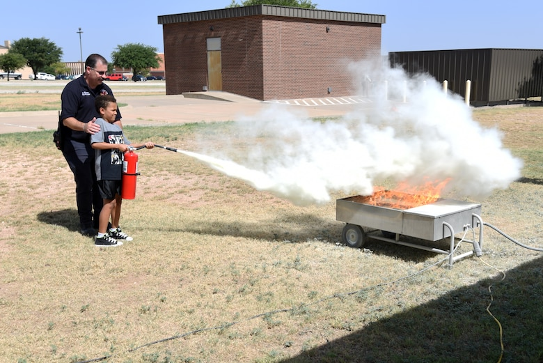 17th Civil Engineer Squadron fire inspector, Billy Clemons, assist junior firefighter, Elijah Scott, with a fire extinguisher during the Junior Firefighter Camp at the Fire Station on Goodfellow Air Force Base, Texas, July 18, 2018. Scott and other junior firefighters learned how to use different extinguishers for different types of fire. (U.S. Air Force photo by Staff Sgt. Joshua Edwards/Released)
