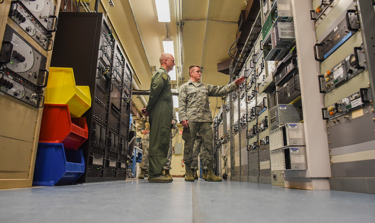 U.S. Air Force Airman 1st Class Randy West, 325th Communications Squadron radio frequency transmission systems apprentice, right, shows off radio equipment to Col. Brian Laidlaw, 325th Fighter Wing commander, left, during an Airman shadow tour in the RF transmission systems shop at Tyndall Air Force Base, Florida, July 16, 2018.