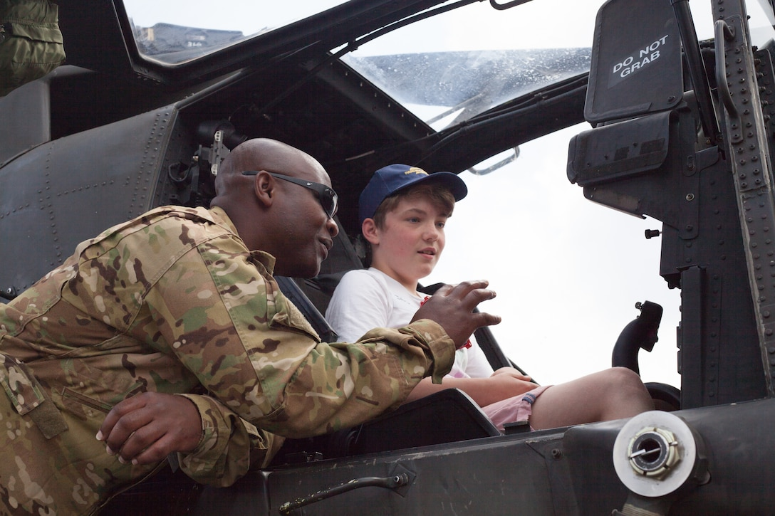 United States military personnel give aircraft tours to children at the Farnborough International Airshow, July 21, 2018 at Farnborough, United Kingdom. Over the weekend, FIA opened up to the general public to demonstrate the latest in military and civilian aircraft capabilities. Farnborough organizers, in conjunction with the Barrie Wells Trust, gave disabled children access to explore various U.S. Air Force and U.S. Army aircraft (U.S. Air Force photo by Capt. Allie Delury)