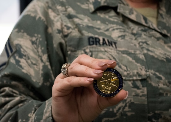 Senior Master Sgt. Rachel Grant holds a coin she received by the commander.