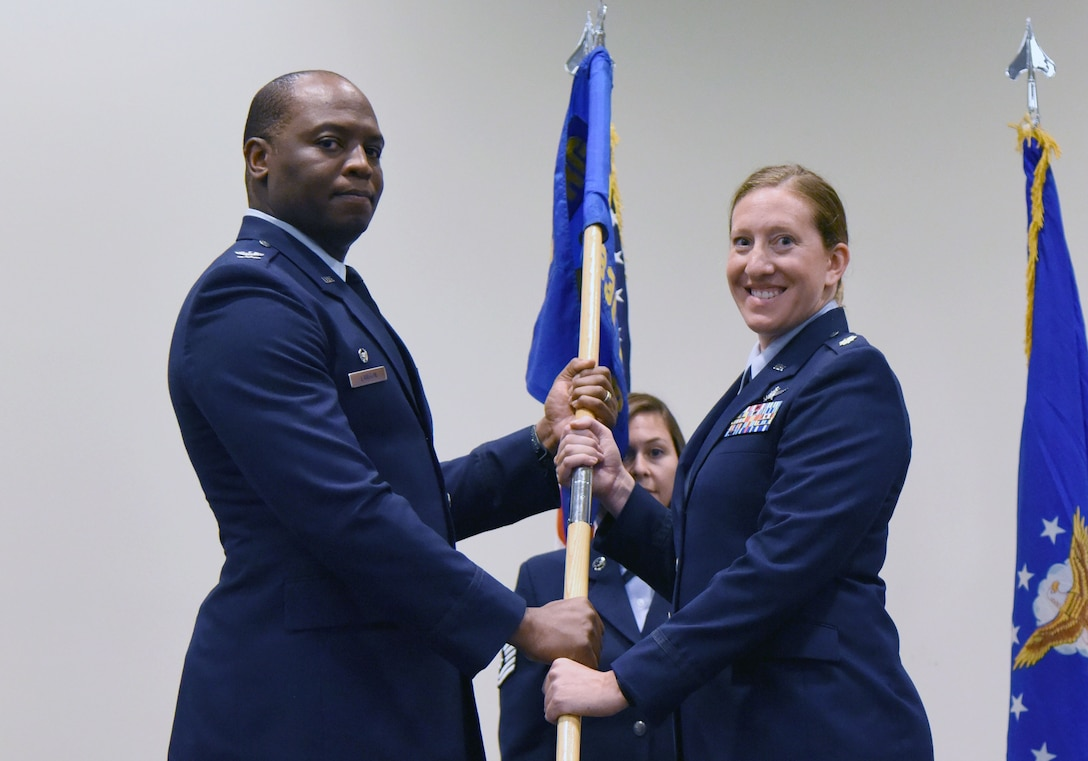U.S. Air Force Col. Leo Lawson, Jr., 81st Training Group commander, passes the 336th Training Squadron guidon to Maj. Jill Heliker, 336th TRS commander, during the 336th TRS change of command ceremony in the Roberts Consolidated Aircraft Maintenance Facility at Keesler Air Force Base, Mississippi, July 23, 2018. The passing of the guidon is a ceremonial symbol of exchanging command from one commander to another. (U.S. Air Force photo by Kemberly Groue)