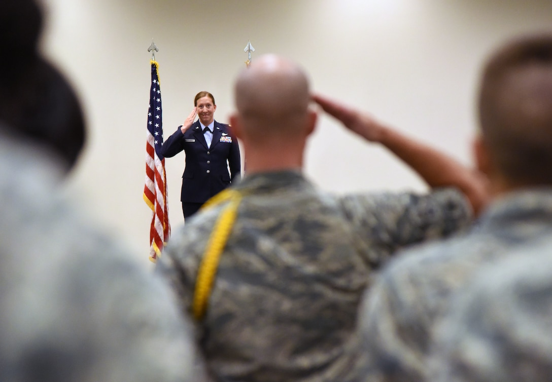 U.S. Air Force Maj. Jill Heliker, 336th Training Squadrom commander, returns a first salute to Airmen during the 336th TRS change of command ceremony in the Roberts Consolidated Aircraft Maintenance Facility at Keesler Air Force Base, Mississippi, July 23, 2018. Heliker assumed command from Lt. Col. Daniel Schmitt, outgoing 336th TRS commander. (U.S. Air Force photo by Kemberly Groue)