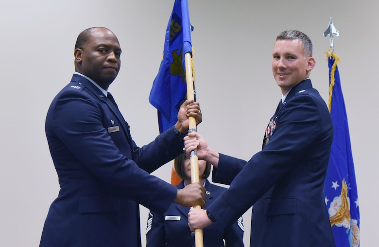 U.S. Air Force Col. Leo Lawson, Jr., 81st Training Group commander, takes the 336th Training Squadron guidon from Lt. Col. Daniel Schmitt, outgoing 336th TRS commander, during the 336th TRS change of command ceremony in the Roberts Consolidated Aircraft Maintenance Facility at Keesler Air Force Base, Mississippi, July 23, 2018. The passing of the guidon is a ceremonial symbol of exchanging command from one commander to another. (U.S. Air Force photo by Kemberly Groue)