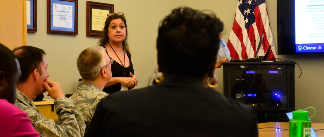 Maria Arroyo, from the Philadelphia Veterans Affairs Regional Office and Insurance Center, left center, briefs benefits information to Medical supply chain military and veteran employees at DLA Troop Support in Philadelphia, July 18, 2018.