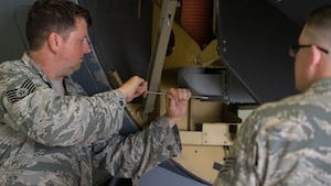 Tech. Sgt. Abraham Partridge, a 403rd Maintenance Squadron intergraded missions systems technician, trains an Airman on avionics equipment at Keesler Air Force Base, Mississippi. Partridge is also a Folk artist and musician. (U.S. Air Force photo by Staff Sgt. Shelton Sherrill)