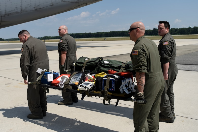 Airmen from the Delaware Air National Guard 142nd Aeromedical Evacuation Squadron carry stretchers with medical equipment July 12, 2018, at Dover Air Force Base, Del. The 142nd AES teamed up with the 9th Airlift Squadron to train aeromedical evacuation procedures on a C-5M Super Galaxy. The 142nd AES is stationed at New Castle Air National Guard Base, Del. (U.S. Air Force photo by Airman 1st Class Zoe M. Wockenfuss)