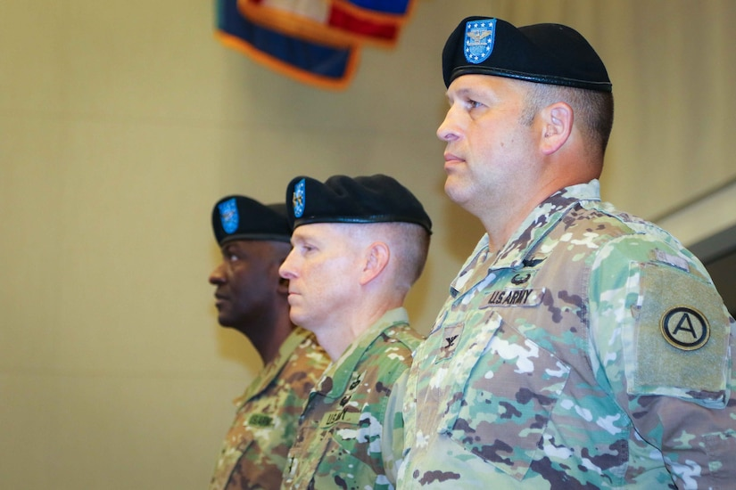 Col. Douglas W. Mills, incoming commander of the 2503rd Digital Liaison Detachment, Maj. Gen. David C. Hill, deputy commanding general, U.S. Army Central, and Col. Oscar W. Doward Jr., outgoing commander of the 2503rd DLD, stand at attention during a change-of-command ceremony July 19, 2018, at Patton Hall on Shaw Air Force Base, S.C. (U.S. Army photo by Sgt. Von Marie Donato)