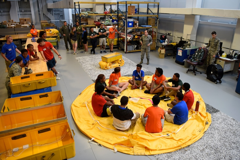 Students of the Aviation Character and Education Flight Program sit inside a life raft during their tour of Aircrew Flight Equipment July 19, 2018, at Dover Air Force Base, Del. The life rafts are able to hold 25 people and are a mandatory item aboard mobility aircraft. (U.S. Air Force photo by Airman 1st Class Zoe M. Wockenfuss)