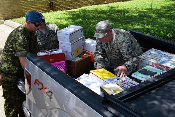 Senior enlisted members assigned to Tyndall Air Force Base, Florida, arrange care packages into the bed of a truck.