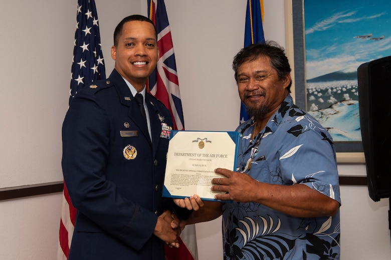 Lt. Col. Wade McGrew, 21st Space Operation sSquadron commander, presents the Air Force Civilian Award for Valor to Robin Albios, Detachment 3, 21st SOPS heating, ventilation and air conditioning specialist, at the Kaena Point Satellite Tracking Station, Hawaii, July 23, 2018. Two years ago, Albios provided medical aid to a state of Hawaii volunteer field crew member who suffered from smoke inhalation during a fire at the Kuaokala Game Management Area. (U.S. Air Force photo by Tech. Sgt. Heather Redman)