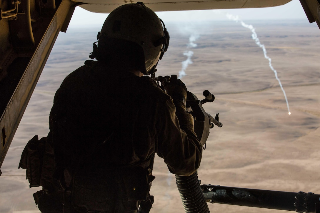 A crew chief fires a machine gun from an aircraft.