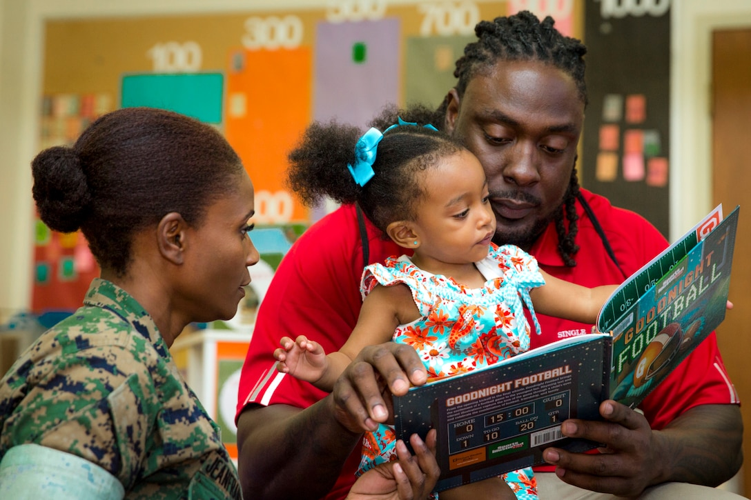 A man holds a toddler and reads her a book as a Marine watches.