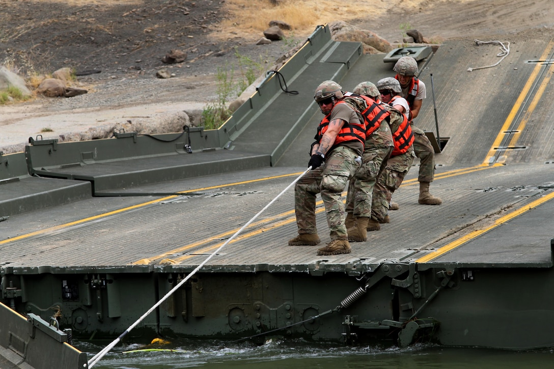 Soldiers pull on a cable while shifting a ramp to dismantle a 100-foot temporary floating bridge.