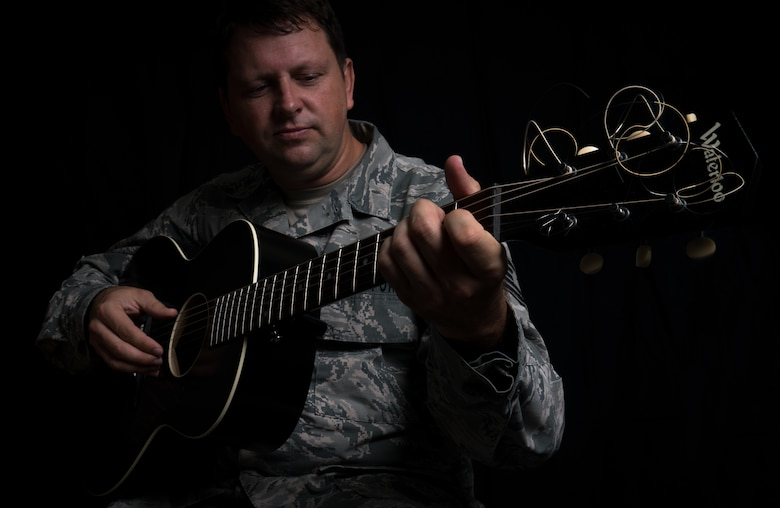 Tech. Sgt. Abraham Partridge, a 403rd Maintenance Squadron intergraded missions systems technician, poses for a portrait with his guitar at Keesler Air Force Base, Mississippi. Partridge's performs Folk music paints Folk art. (U.S. Air Force photo by Staff Sgt. Shelton Sherrill)