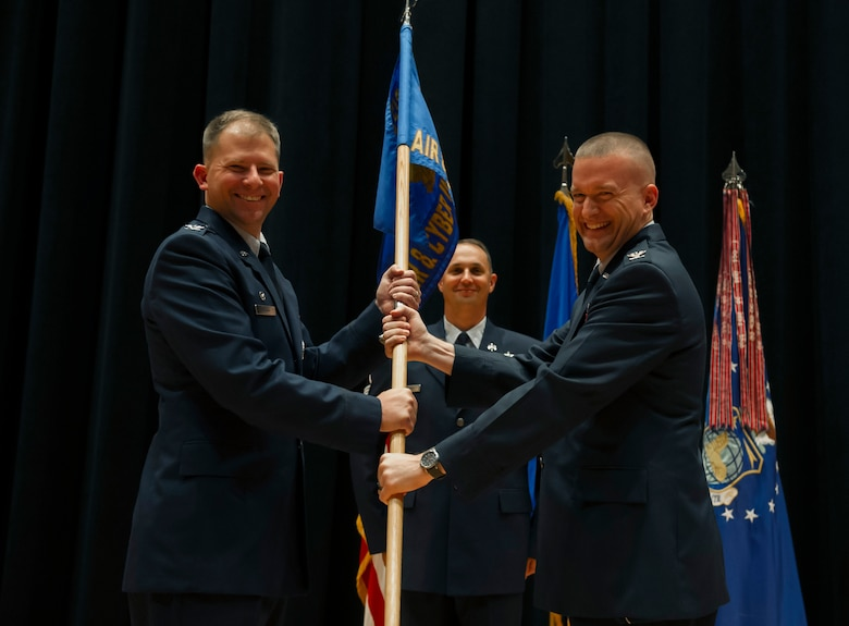 Col. William Fry accepts command of the National Air and Space Intelligence Center's Air and Cyberspace Intelligence Group from Col. Parker Wright, NASIC commander, July 20. AC is responsible for the production of original intelligence assessments on foreign air systems, electronics, directed energy, integrated air defense, and cyberspace systems supporting the warfighter, national policy makers and the acquisitions community. (U.S. Air Force photo/ Senior Airman Jonathan Stefanko)
