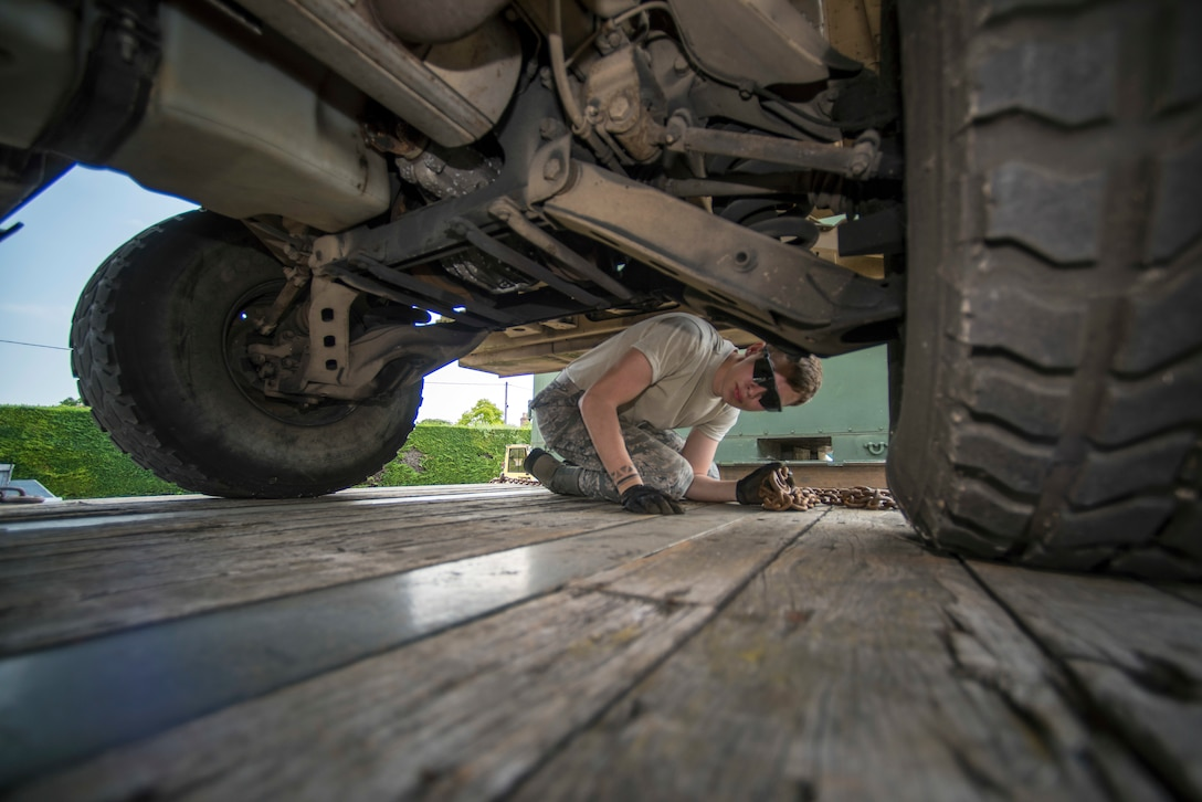 U.S. Air Force Airman 1st Class Dennis Fite, 100th Logistics Readiness Squadron ground transportation operator, ensures a HUMVEE is properly loaded on a trailer at RAF Mildenhall, England, July 20, 2018. Technical training for ground transportation Airmen is just under a month long, where they learn how to tie down heavy equipment and how to drive a variety of vehicles. (U.S. Air Force photo by Senior Airman Christine Groening)