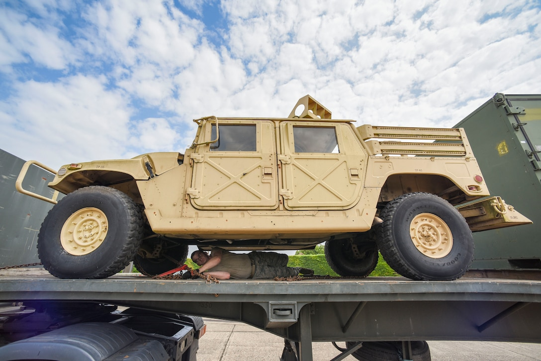 U.S. Air Force Airman 1st Class Brinkley Owens, 100th Logistics Readiness Squadron ground transportation operator, conducts tie down procedures on a HUMVEE on RAF Mildenhall, England, July 20, 2018. Chains keep the vehicle more secure on the trailer, rather than using regular tie down straps. (U.S. Air Force photo by Senior Airman Christine Groening)