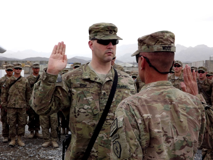 Soldier raises his hand at re-enlistmnent ceremony.