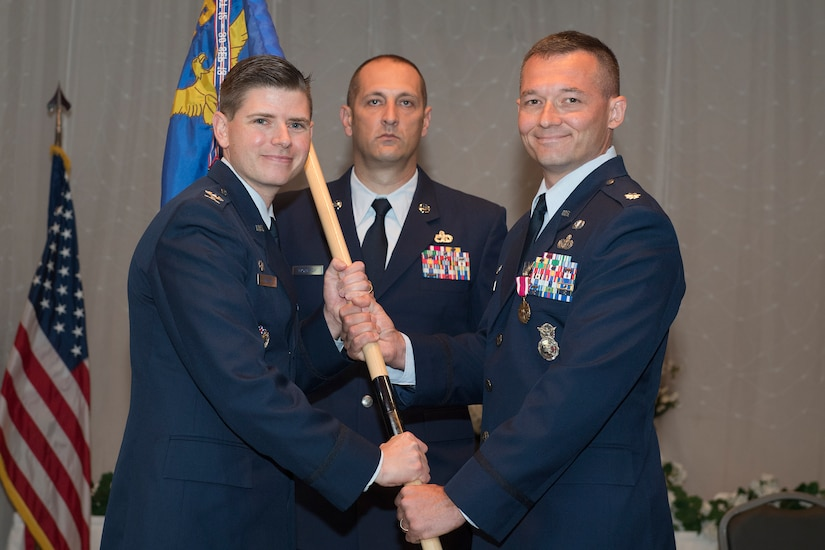 Lt. Col. Michael Speck, right, 628th Security Forces Squadron incoming commander, assumes command and accepts the squadron's guidon from Col. Rockie Wilson, left, 628th Mission Support Group commander, during a change of command ceremony here at the Red Bank Club, July 23, 2018.